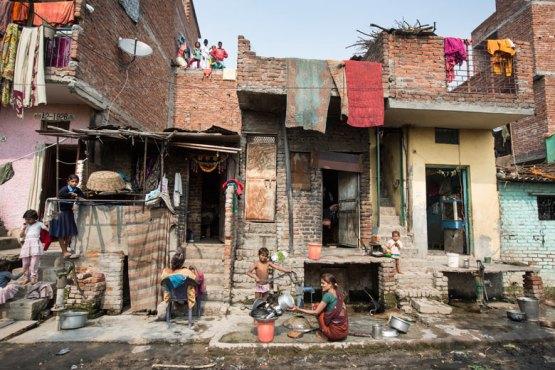 Children play outside their slum homes